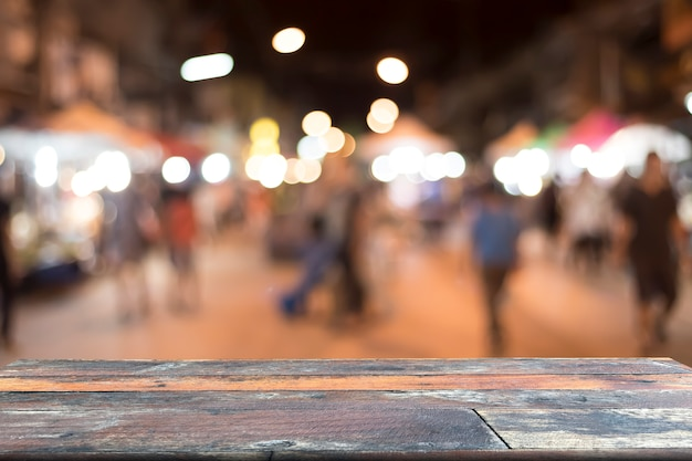 Empty wooden table for present on blurred walking street background