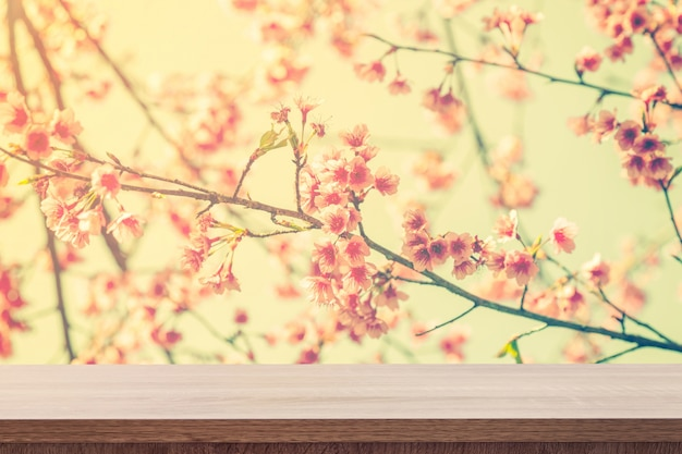 Empty wooden table for product placement or montage and pink blossom with vintage toned.