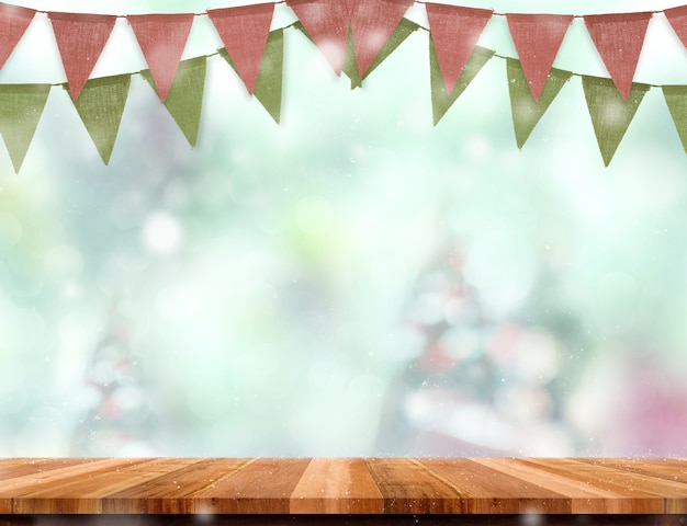 Empty wooden table and red green banner flag with abstract blur christmas tree and snow fa