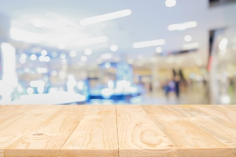 Empty wooden table space platform with blurred shopping mall or shopping center background for product display montage. Wooden desk with copy space.