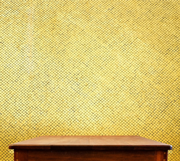 Empty wooden table top at golden mosaic tiles wall,template mock up for display of your product
