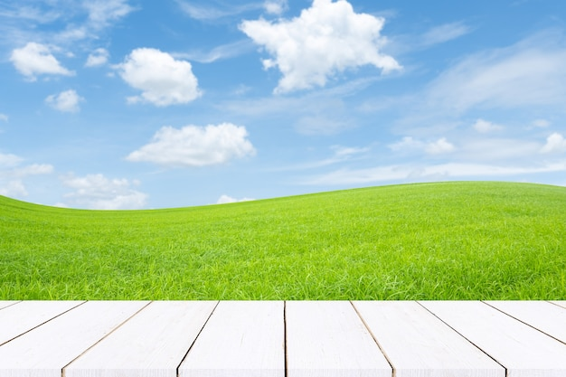 Empty wooden table top. greenfield and blue sky with light clouds, sunset summer field.