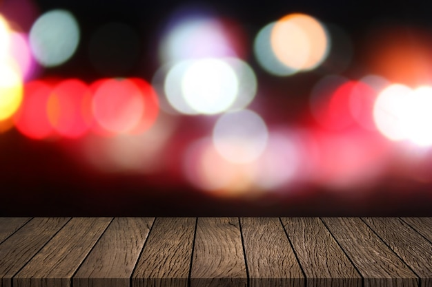 Empty wooden table top with abstract night blurred bokeh city street lights background