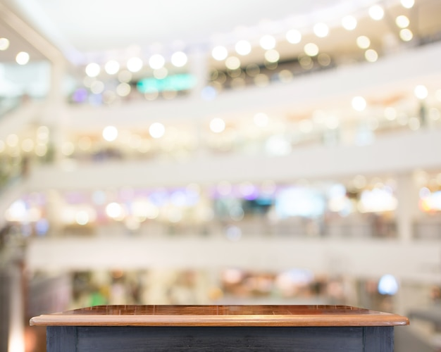 ぼんやりとした木製のテーブルトップ、ぼんやりした店の背景、あなたのプロダクトを表示するためのテンプレートモックアップ、ビジネスプレゼンテーション