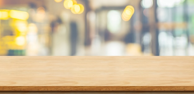 Empty wooden table top with blurred cafe background