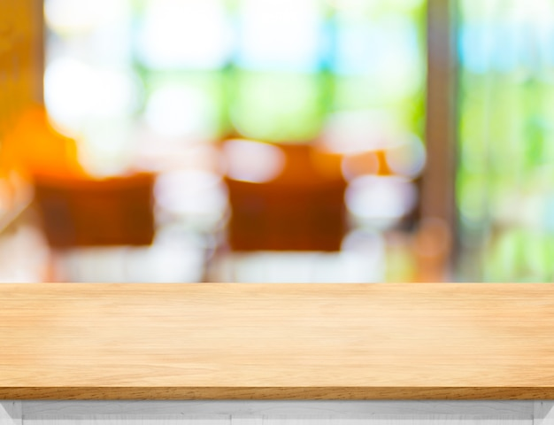 Empty wooden table top with blurred cafe bokeh light as background
