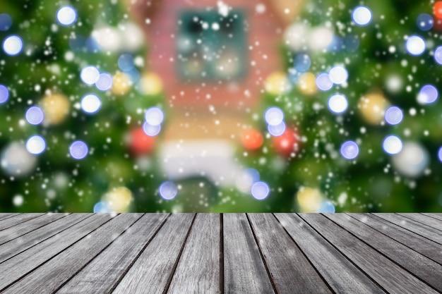 ぼやけたクリスマスツリーの背景と空の木製テーブルトップ