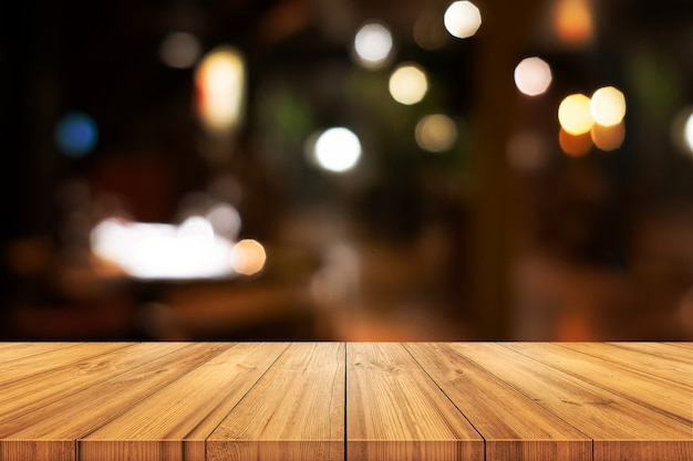 흐리게 커피 숍 또는 레스토랑 인테리어 배경으로 가기 빈 나무 테이블. 제품 디스플레이를 사용할 수 있습니다.