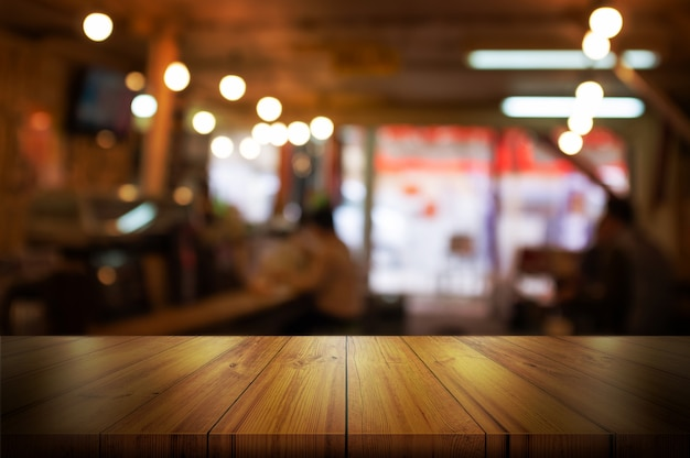 Empty wooden table top with blurred coffee shop or restaurant interior background.