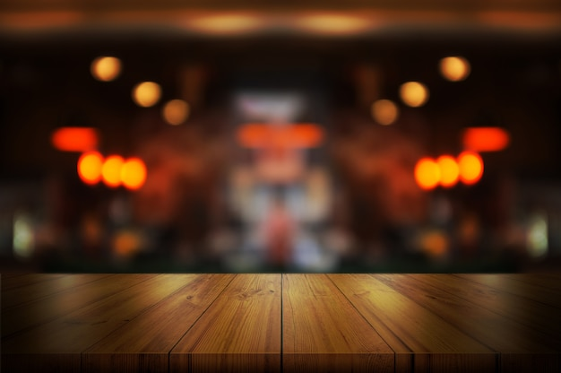 Empty wooden table top with blurred coffee shop.