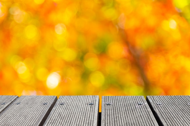Empty wooden table top with colorful color of garden bokeh for creating.