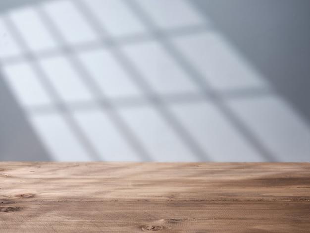 창에서 빛이 들어오는 빈 나무 탁자