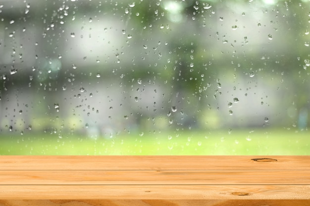 Empty wooden table over water drop on window garden background