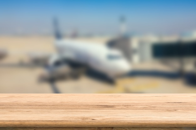 Empty wooden table with airplane blurred background