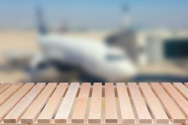 비행기 배경이 흐릿한 빈 나무 테이블