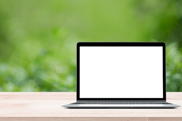 Empty wooden table with blank screen laptop on green blurred background from foliage