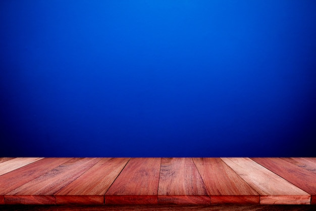 Empty wooden table with blue wall texture background