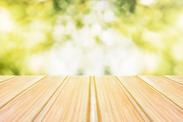 Empty wooden table with blurred city park on background.
