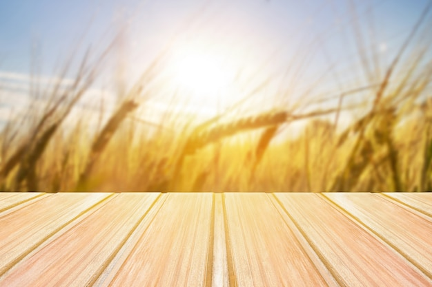 Empty wooden table with blurred grasses, grain on background