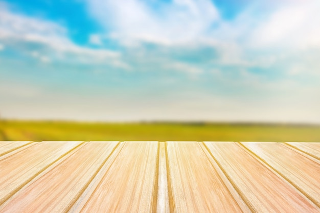 Empty wooden table with blurred green field on background and blue sky
