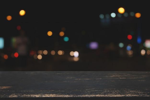 Пустой деревянный стол с размытым ночным боке фон