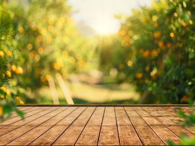 ぼやけたオレンジの木と空の木製テーブル