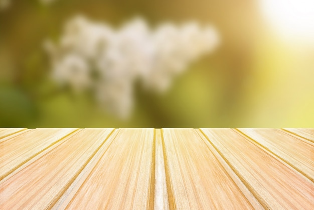 Empty wooden table with blurred spring background, bokeh of flowers and park
