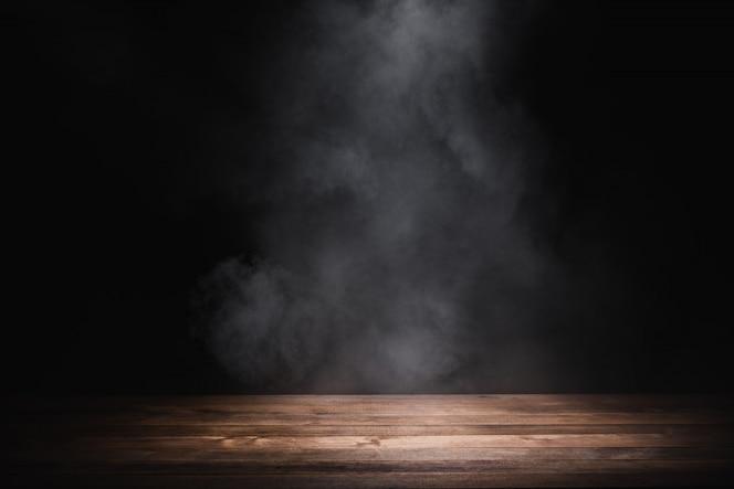 연기와 함께 빈 나무 테이블은 어두운 배경에 떠