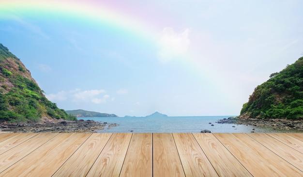 空の木製卓上と海の背景の上の虹と熱帯のビーチを表示