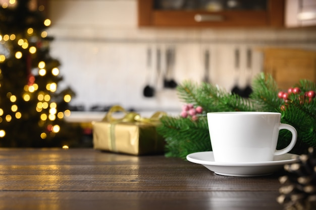 Empty wooden tabletop with cup of coffee and blurred modern kitchen with christmas tree.