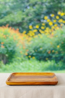 흐림 나무 배경 위에 리넨 식탁보와 테이블에 빈 나무 트레이