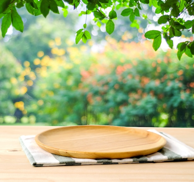 Empty wooden tray on table over blur green park background