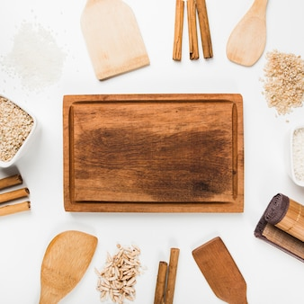 Empty wooden tray with spatula; rice; cinnamon sticks on white background