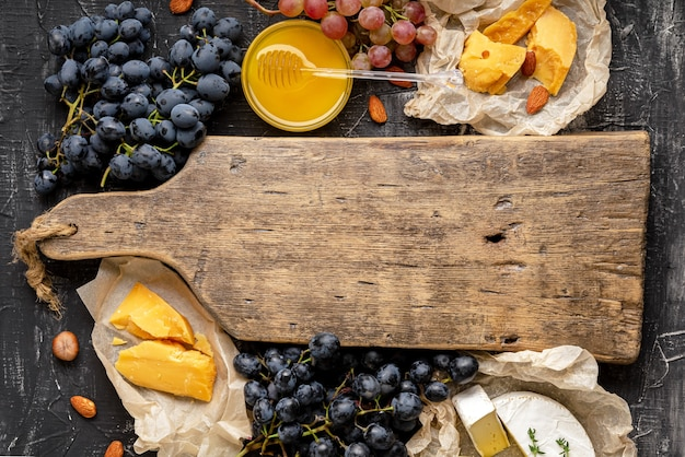 Empty wooden vintage cutting board in center of frame made of honey grapes cheese snack other ingredients gastronomy snacks. mock up copy space or template on brown cutting board for grocery shop.