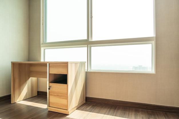 Пустой рабочий стол в комнате с окном Premium Фотографии