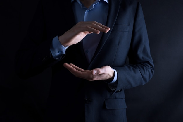 An empty workpiece. a businessman in a suit on a black background holds his hands protective gesture