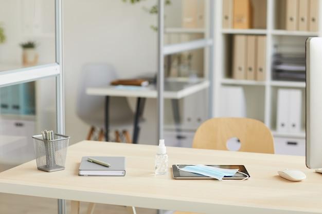 Пустой рабочий стол с маской для лица и дезинфицирующим средством для рук в офисе после пандемии