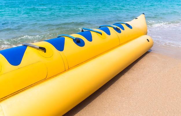 青い海と砂の上の空の黄色いバナナボート。海タイのコンセプトで休日にリラックス。