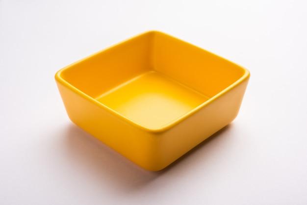 白または灰色の表面上に分離された空の黄色のセラミックサービングボウル