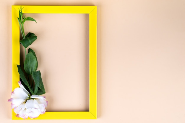 Empty yellow frame and flowers eustoma on beige paper background with copy space
