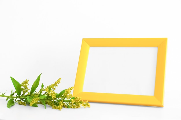 Empty yellow frame and flowers on white background