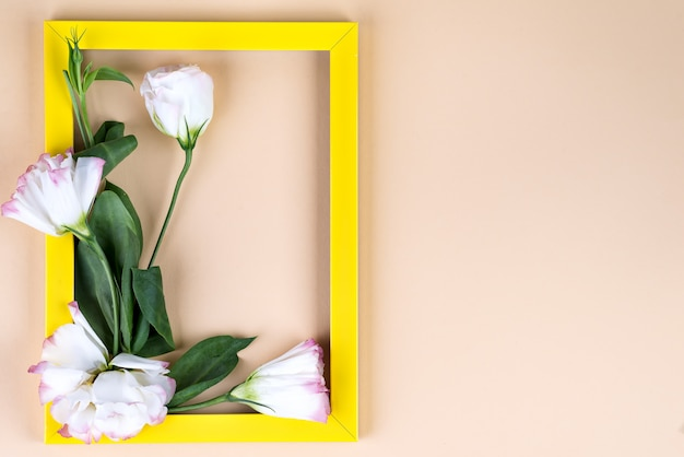 Empty yellow frame and flowers