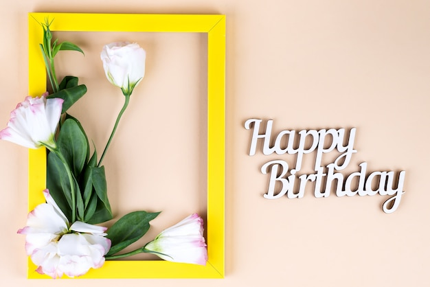 Empty yellow frame, happy birthday letter and flowers eustoma on beige surface with copy space.