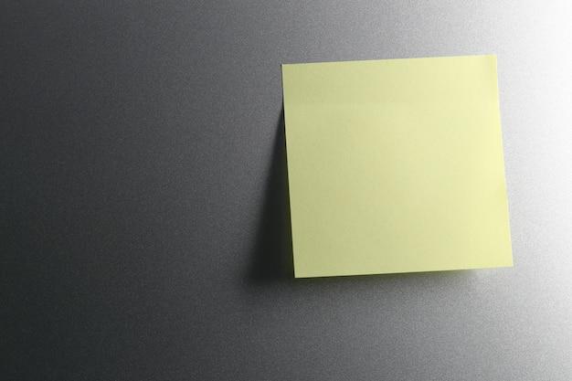 Empty yellow paper sheet on refrigerator door for design.