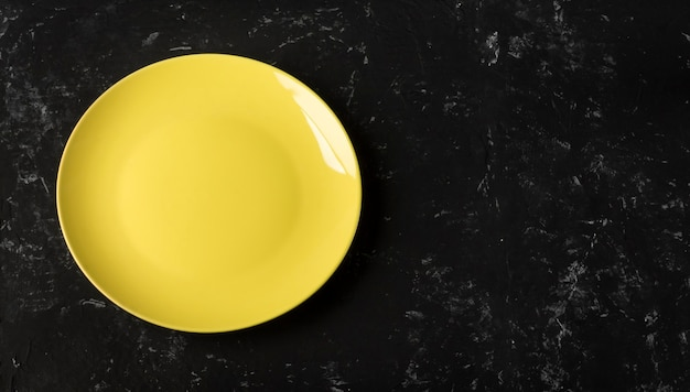 An empty yellow plate on a black textured background with a copy of the space.