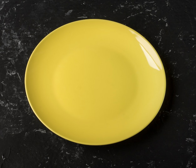 An empty yellow plate on a black textured background.