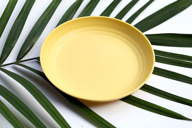 Empty yellow plate on tropical palm leaves on white background.