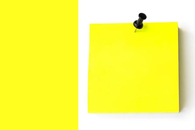빈 노란색 게시물 흰색 노란색 배경에 검은색 핀으로. 빈 노란색 스티커 메모입니다.