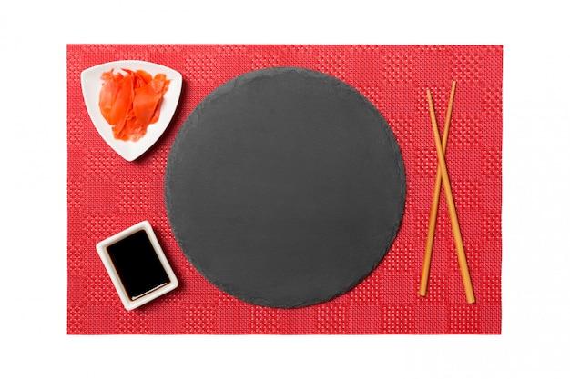 Пустая круглая черная тарелка с палочками для суши и соевым соусом, имбирь на красных матовых суши. вид сверху с копией пространства для вашего дизайна