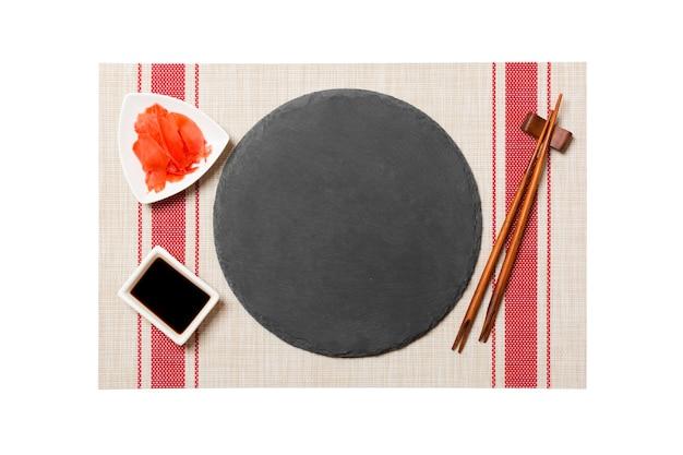 Пустая круглая черная шиферная тарелка с палочками для суши и соевого соуса, имбирь на фоне циновки для суши. вид сверху с копией пространства для вашего дизайна.